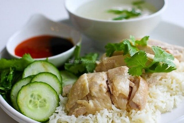 Chicken rice. For those not from Malaysia or Singapore, chicken rice is a yummy meal of rice cooked in chicken stock & garlic, steamed or roast chicken, served with sliced cucumber, soup, chilli & ginger sauce.